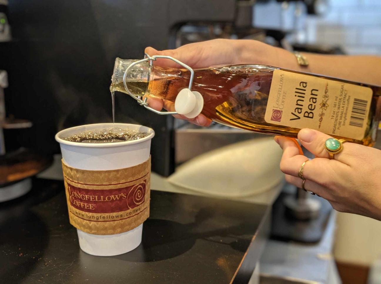 Pouring house-made syrup into a coffee cup with a logo
